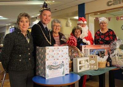 Kathryn Lawrence, Richard Dodd, Chrysanda Gilbert, Doris Froggatt, Santa and Heather Green standing next to the raffle prizes