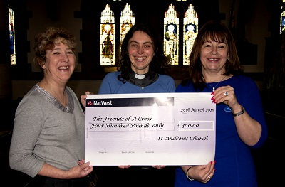 Kathryn Lawrence (L) and Tracey Lennard (R) decorated the Friends tree and are pictured receiving the cheque from the Reverend Imogen Nay.