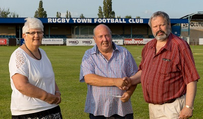 Tony Mann presents a cheque to Heather Green and Willy Goldschmidt at Rugby Town FC